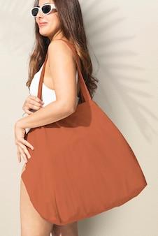 Schöne frau, die eine braune einkaufstasche trägt, bereit für den strand
