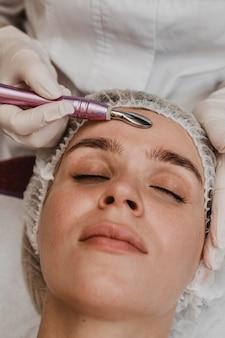 Schöne frau, die eine kosmetische behandlung hat
