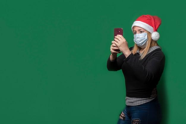 Schöne frau, die eine maske und einen roten hut an weihnachten während eines videoanrufs mit handy trägt