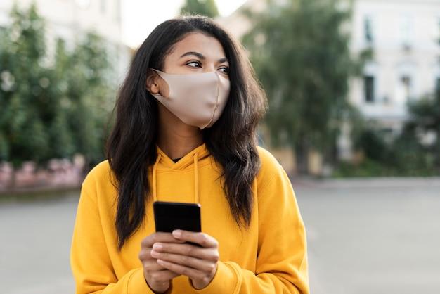 Schöne frau, die eine medizinische maske im freien trägt