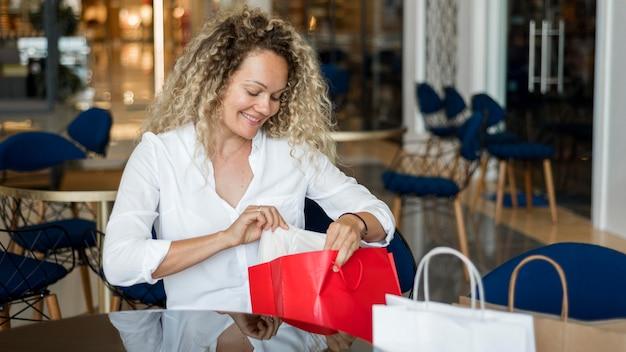 Schöne frau, die eine pause nach dem einkaufen macht