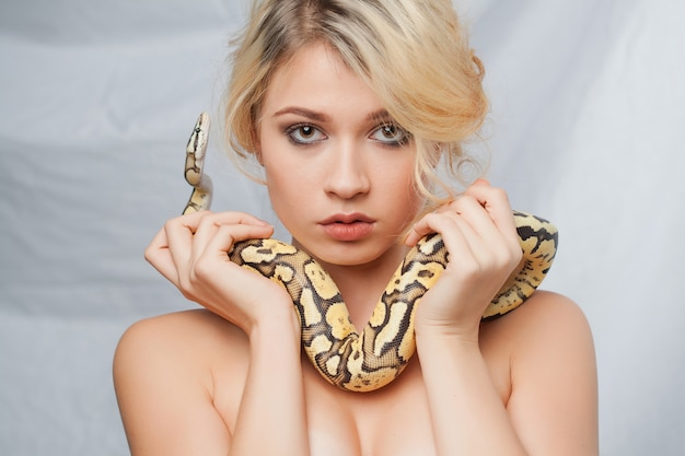 Schöne frau, die eine pythonschlange anhält, die um ihren körper einwickelt