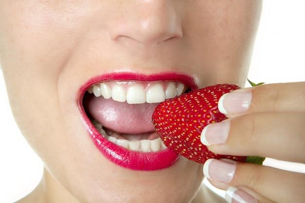 Schöne frau, die eine rote erdbeere isst
