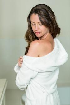 Schöne frau, die eine schulter beim ausziehen ihres bademantels herausstellt