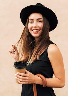 Schöne frau, die eine tasse kaffee hält