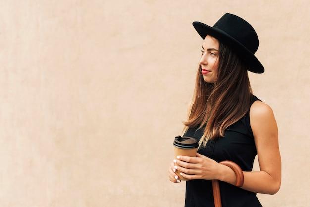 Schöne frau, die eine tasse kaffee mit kopienraum hält