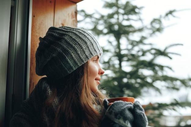 Schöne frau, die eine tasse kaffee oder kakao in handschuhen hält und trinkt, die nach hause am fenster sitzen. unscharfer winterschneebaumhintergrund.