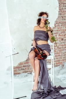 Schöne frau, die eine violine anhält und rotrose riecht