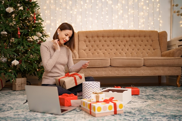 Schöne frau, die eine weihnachtsgrußkarte liest, während sie zwischen geschenkboxen sitzt.