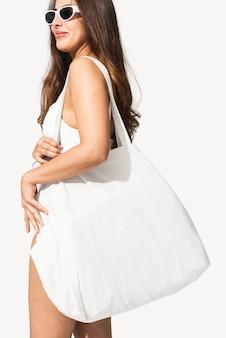 Schöne frau, die eine weiße einkaufstasche trägt, bereit für den strand