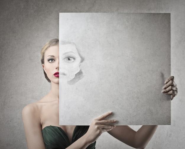 Schöne frau, die eine zeichnung ihres gesichtes anhält