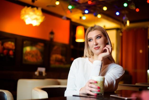 Schöne frau, die einen cappuccino in einem café trinkt