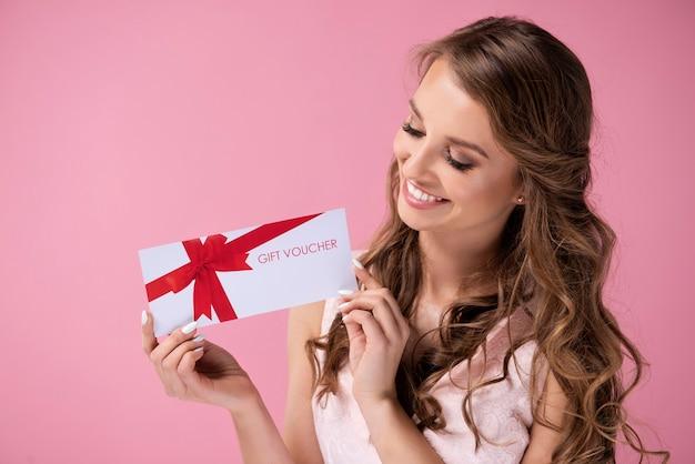 Schöne frau, die einen geschenkgutschein verschenkt
