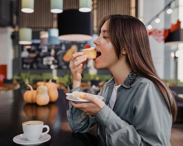 Schöne frau, die einen kaffee und kuchen genießt