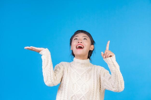 Schöne frau, die einen neuen langärmeligen weißen teppich, eine geste auf einem blau zeigend trägt. handeln.