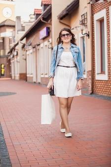 Schöne frau, die einkaufen und auf der alten straße spazieren geht