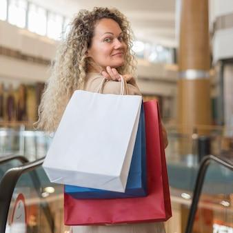 Schöne frau, die einkaufstaschen am einkaufszentrum trägt