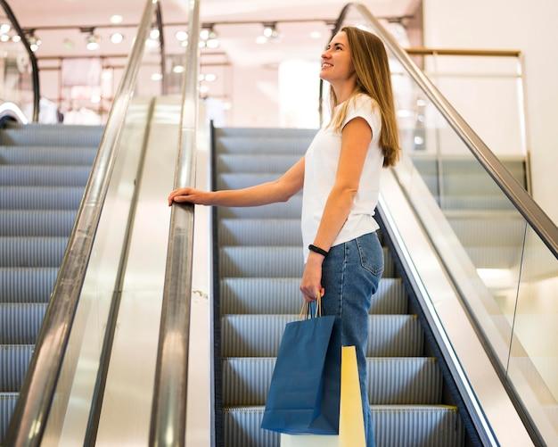 Schöne frau, die einkaufstaschen trägt