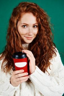 Schöne frau, die einwegbecher kaffee hält