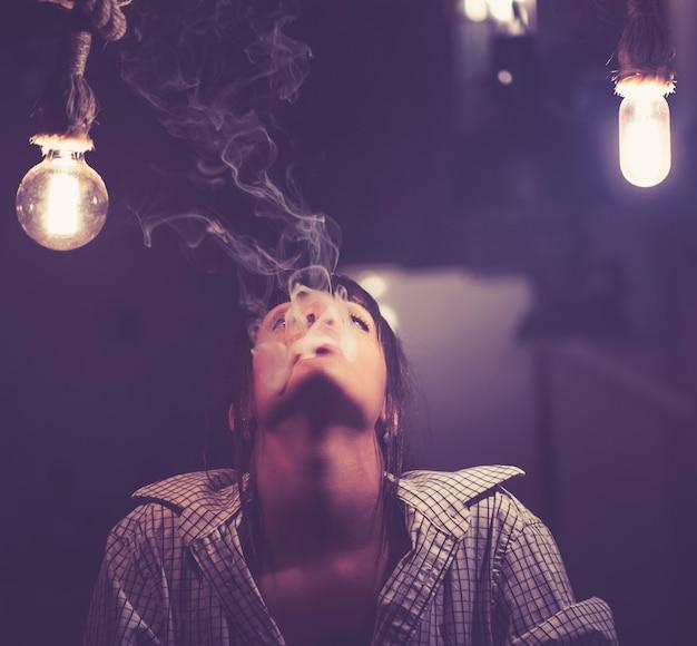 Schöne frau, die elektronische zigarette raucht