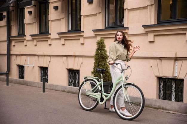 Schöne frau, die entlang ihres fahrrads in der stadt geht