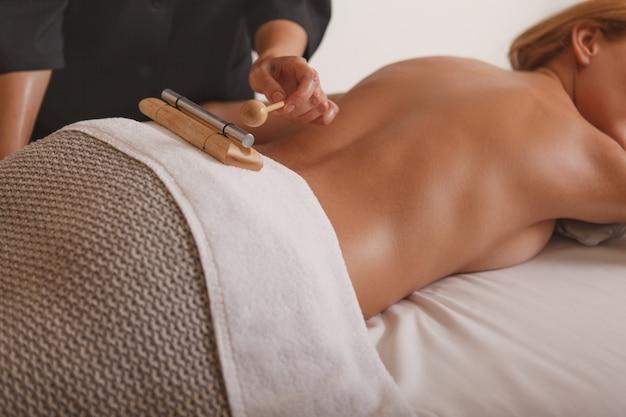 Schöne frau, die entspannende massage in der badekurortmitte empfängt