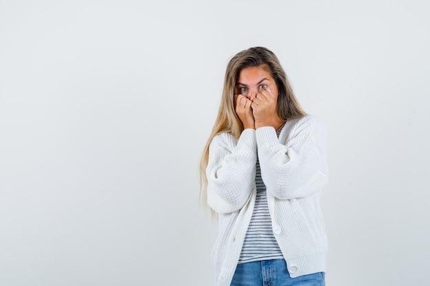 Schöne frau, die fäuste auf gesicht in jacke, t-shirt hält und überwältigt, vorderansicht schaut.