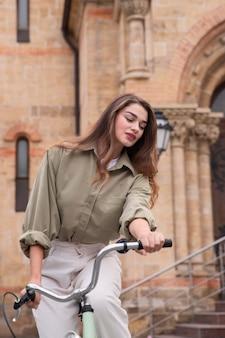 Schöne frau, die fahrrad in der stadt reitet