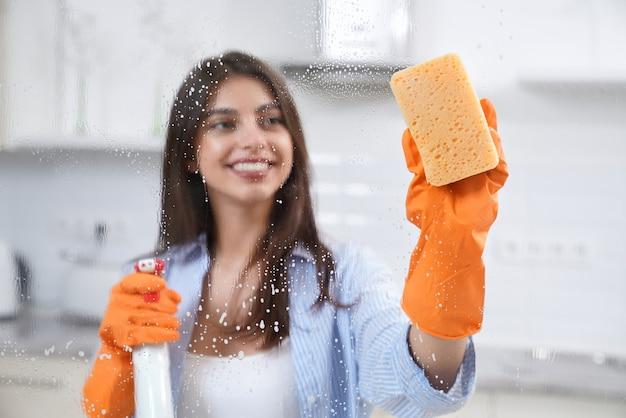 Schöne frau, die fenster mit waschmittel wäscht