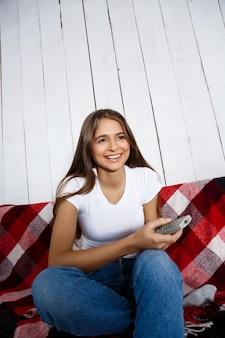 Schöne frau, die fernsieht, lächelt und zu hause auf sofa sitzt.
