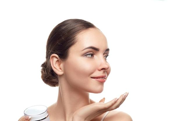 Schöne frau, die feuchtigkeitscreme hält. kosmetika. porträt der frau mit sauberer haut. hautpflege. gesichtsbehandlung. kosmetologie, schönheit und spa