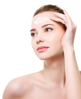 Schöne frau, die feuchtigkeitscremekosmetik auf stirn anwendet
