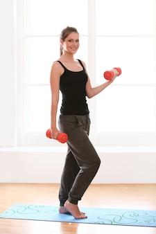 Schöne frau, die fitness-training zu hause macht