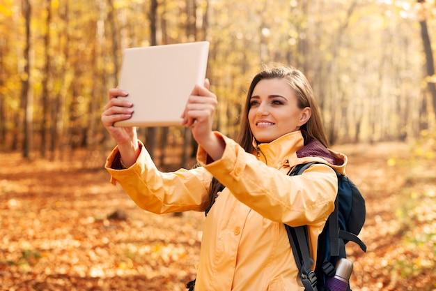 Schöne frau, die foto durch digitales tablett nimmt