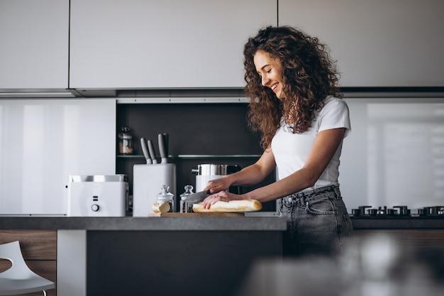 Schöne frau, die frisches brot an der küche isst