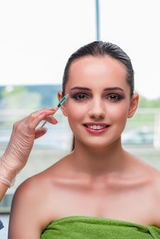 Schöne frau, die für botox einspritzung sich vorbereitet