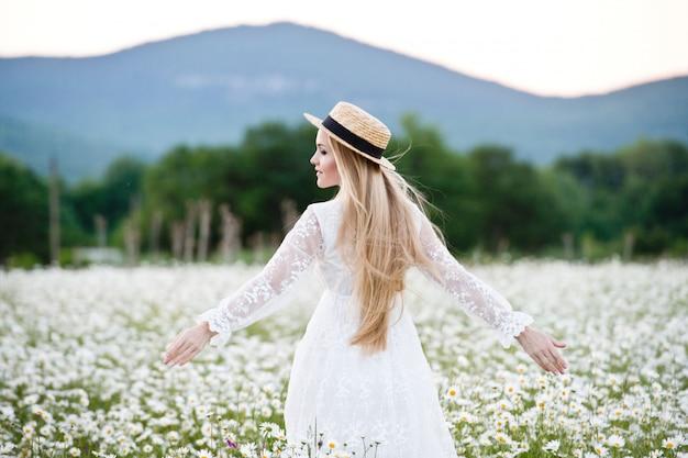 Schöne frau, die gänseblümchenfeld genießt. blonde frau mit strohhut und blumenstrauß.