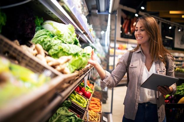 Schöne frau, die gemüse gesundes essen im supermarkt kauft