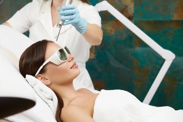 Schöne frau, die gesichtsbehandlung mit laser im schönheitssalon durch kosmetikerin erhält