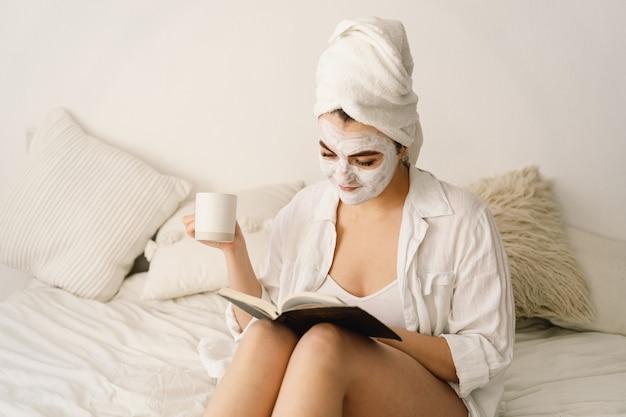 Schöne frau, die gesichtsmaske anwendet, buch liest und tee im bett trinkt.