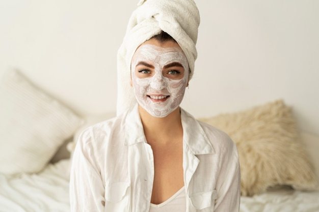 Schöne frau, die gesichtsmaske anwendet. kosmetik.