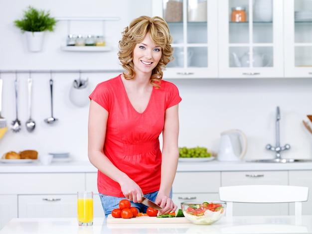 Schöne frau, die gesundes essen in der küche vorbereitet