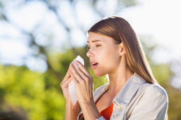 Schöne frau, die gewebe beim niesen verwendet