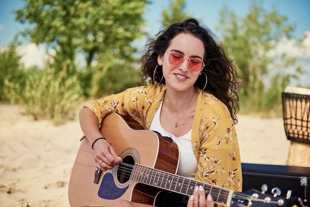 Schöne frau, die gitarre am strand spielt