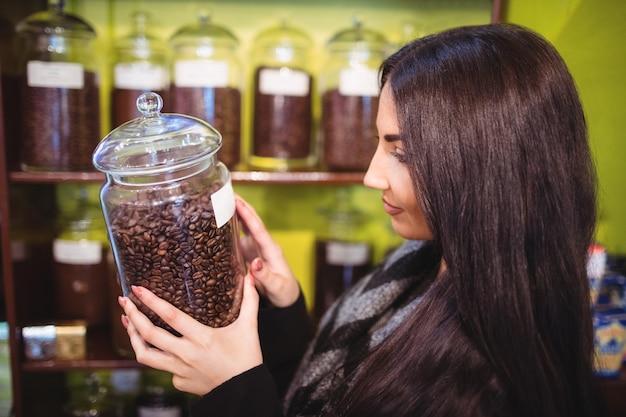 Schöne frau, die glas kaffeebohnen hält