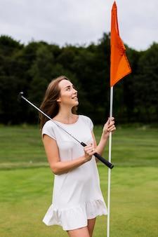 Schöne frau, die golfpfosten anhält