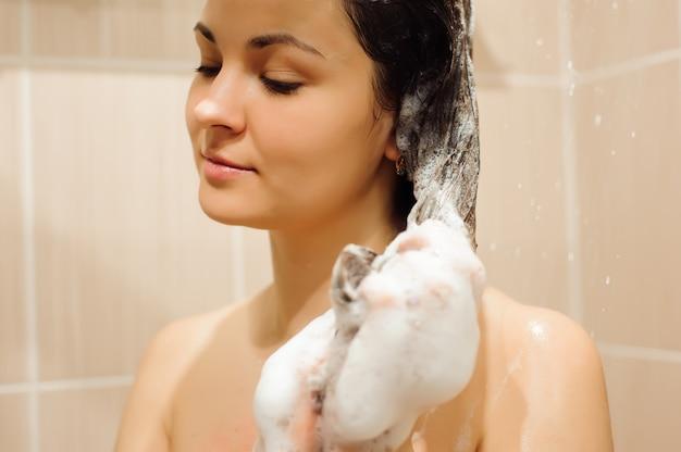 Schöne frau, die haare mit shampoo wäscht
