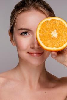 Schöne frau, die halbiertes orange hält