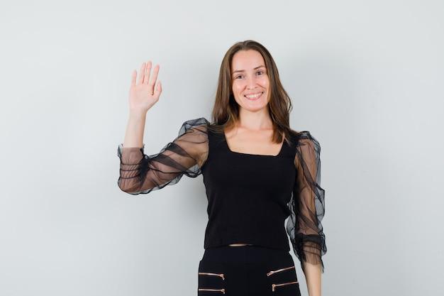 Schöne frau, die hand oben in der schwarzen bluse erhebt und fröhlich schaut. vorderansicht.