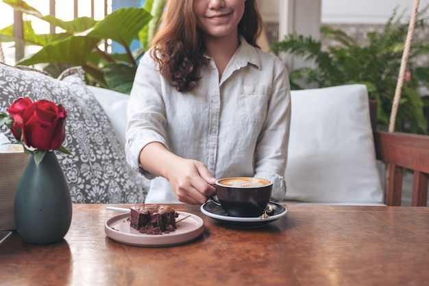 Schöne frau, die heißen lattekaffee mit brownie-kuchen auf dem tisch im café hält und trinkt